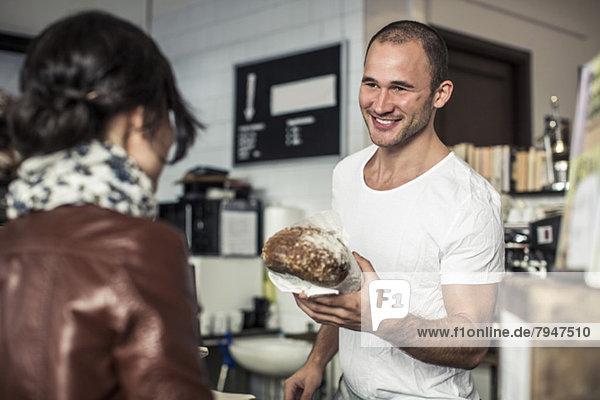 Glücklicher junger  männlicher Besitzer  der dem Kunden in der Bäckerei Brot gibt.