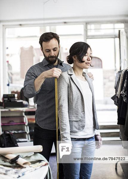 Mittlerer Erwachsener männlicher Modedesigner  der die Schulter der Frau im Studio misst