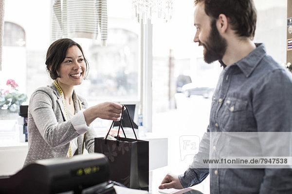 Mittlerer Erwachsener weiblicher Design-Profi  der dem Kunden an der Kasse im Studio eine Einkaufstasche schenkt.