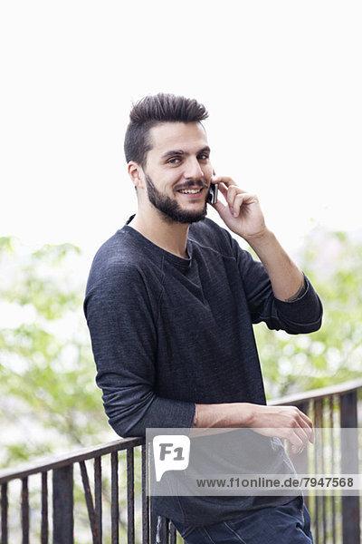 Porträt eines glücklichen Mannes  der sein Handy benutzt  während er sich auf das Geländer stützt.