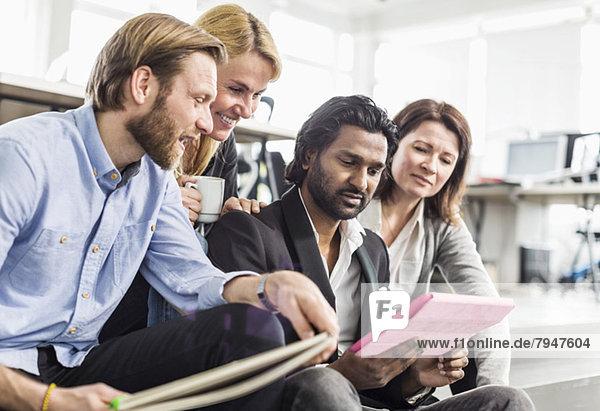 Mittelständischer Geschäftsmann mit digitalem Tablett und Kollegen im Büro