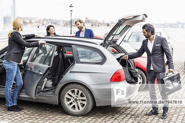 Kollegen diskutieren  während Geschäftsmann Taschen aus dem Auto lädt