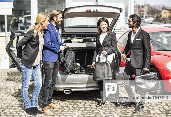 Geschäftsleute kommunizieren beim Entladen von Taschen aus dem Kofferraum.
