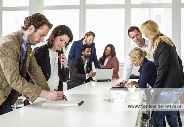 Geschäftsleute diskutieren bei der Arbeit am Schreibtisch im Büro