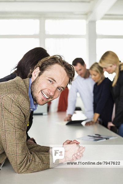 Portrait of happy mid adult businessman leaning on desk with colleagues in background