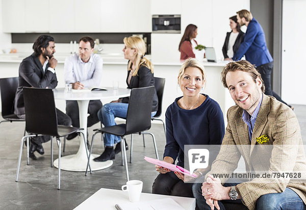 Portrait von glücklichen Geschäftsleuten mit Kollegen  die im Hintergrund im Bürorestaurant diskutieren.