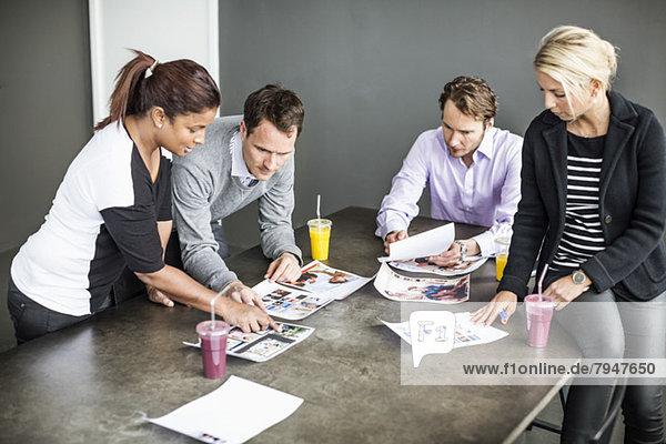 Multiethnische Geschäftsleute diskutieren über Fotos am Schreibtisch im Büro