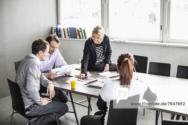 Mittlere erwachsene Geschäftsfrau schaut sich Fotos an  während sie mit Kollegen im Büro am Tisch diskutiert.