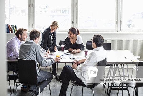 Gruppe von Geschäftskollegen diskutiert am Schreibtisch im Büro