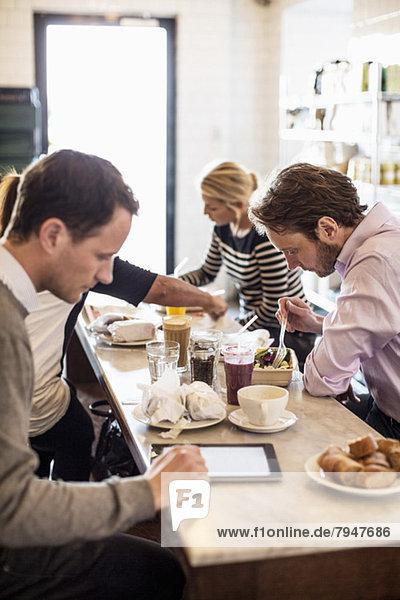 Mittlerer erwachsener Geschäftsmann mit digitalem Tablett und Kollegen beim Frühstück am Restauranttisch