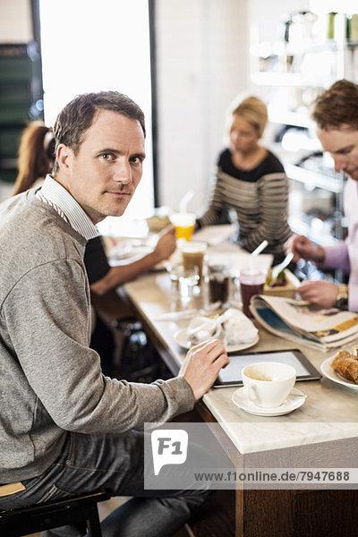 Porträt eines mittelständischen Geschäftsmannes mit Kollegen beim Frühstück im Bürorestaurant