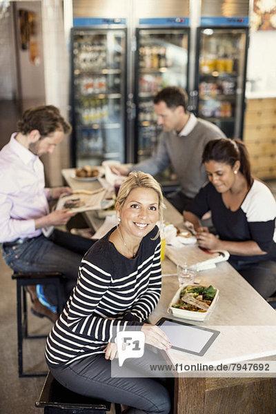 Hochwinkliges Porträt einer selbstbewussten Geschäftsfrau mit digitalem Tablett und Kollegen beim Frühstück im Hintergrund am Restauranttisch.