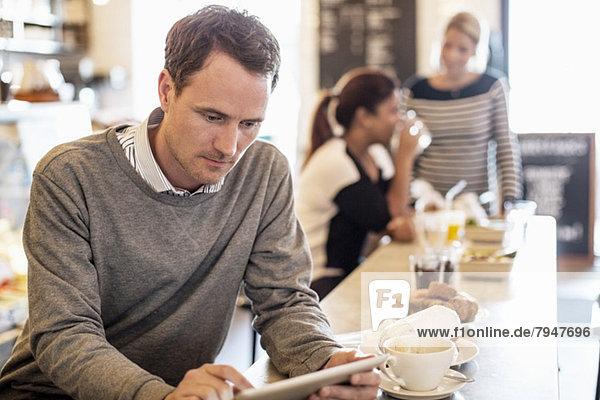 Mittlerer erwachsener Geschäftsmann mit digitalem Tablett am Restauranttisch mit Kollegen im Hintergrund