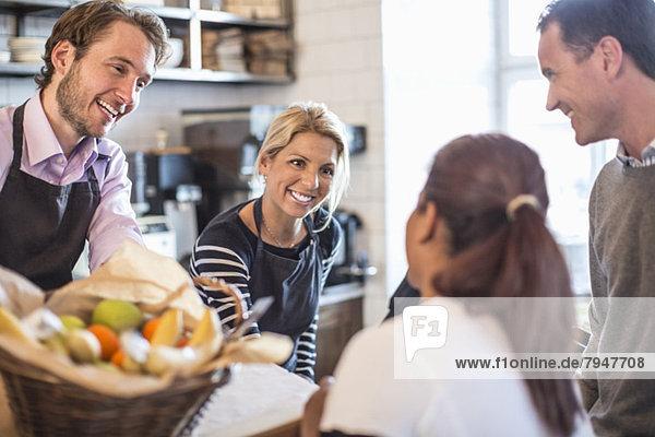 Besitzerin und Besitzerin bei der Kundenbetreuung am Schalter im Restaurant