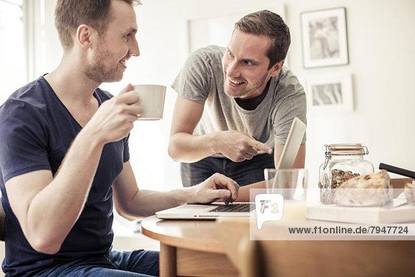 Homosexuelles Paar mit Laptop zusammen am Frühstückstisch zu Hause