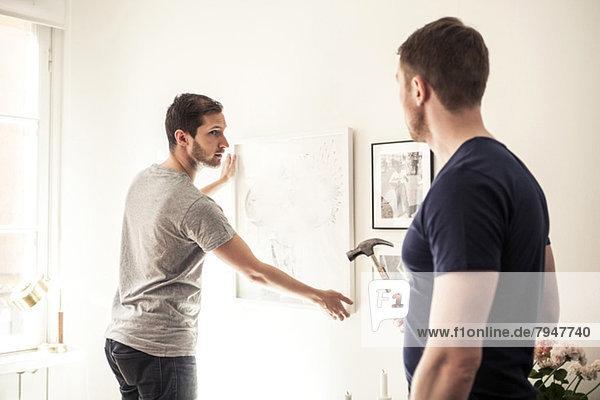 Junger schwuler Mann  der den Partner ansieht  während er zu Hause den Rahmen an die Wand hängt.