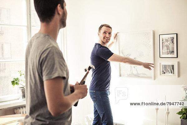Seitenansicht des jungen schwulen Mannes  der den Partner beim Aufhängen des Rahmens an der Wand im Haus ansieht.