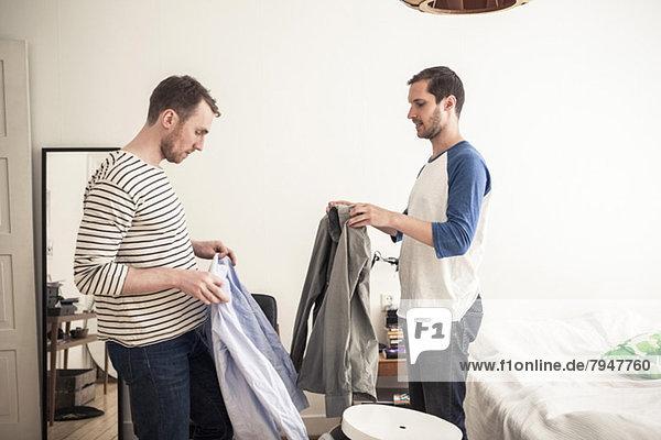 Seitenansicht eines homosexuellen Paares mit Hemden im Schlafzimmer