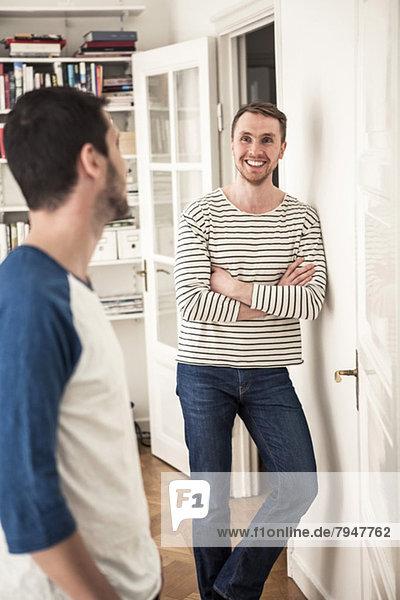 Junger schwuler Mann mit verschränkten Armen beim Anblick des Partners im Haus