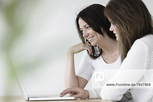 Junge Freundinnen  die den Laptop gemeinsam am Tisch im Haus benutzen