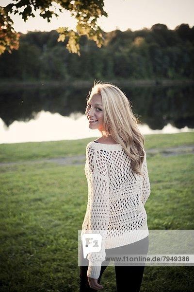 Frau  lächeln  über  spät  Fluss  jung  Nachmittag  Wiese  Bank  Kreditinstitut  Banken  Sonne