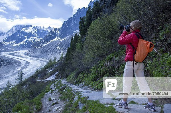 A female photographer as seen on sunny afternoon on a trail above Mer de Glace in Chamonix  France on June 1 2012.