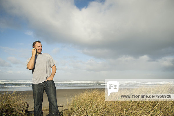 Man on phone while standing on beach