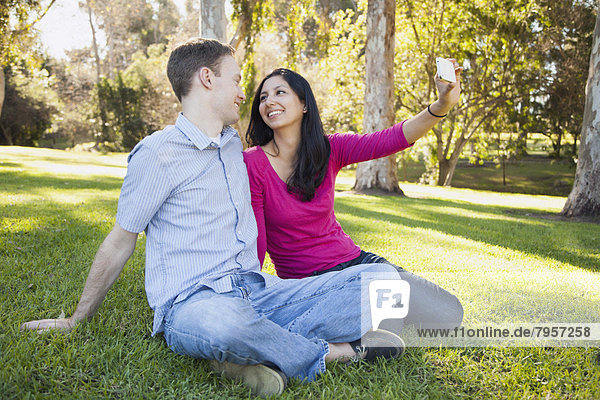 Couple sitting on grass in park photographing themselves