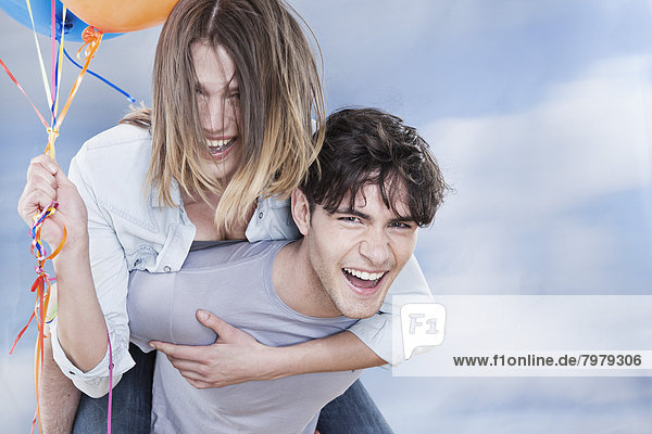 Young man giving piggyback ride to woman  smiling