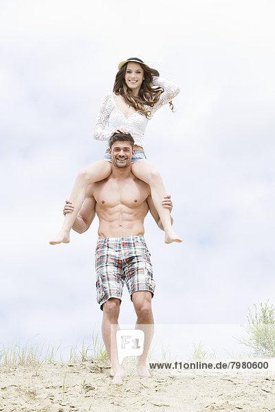 Junger Mann mit Frau auf der Schulter