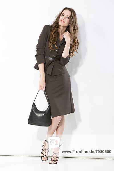 Porträt einer jungen Geschäftsfrau mit Handtasche  lächelnd