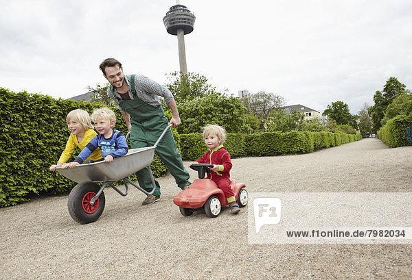 Deutschland  Köln  Vater mit Tochter und Sohn in Schubkarre  lächelnd