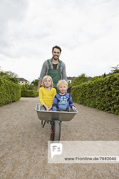 Deutschland  Köln  Vater mit Sohn in Schubkarre  lächelnd