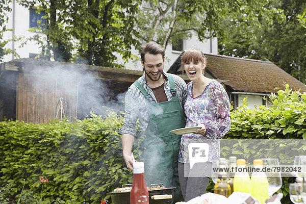 Deutschland  Köln  Junges Paar grillen  lächeln