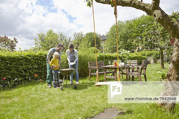 Deutschland  Köln  Familie beim Grillen im Garten