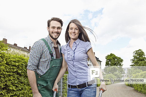 Deutschland  Köln  Portrait eines jungen Paares mit Schubkarre  lächelnd