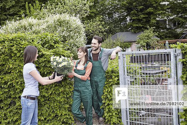 Junges Paar schenkt Topfpflanze an junge Frau  lächelnd