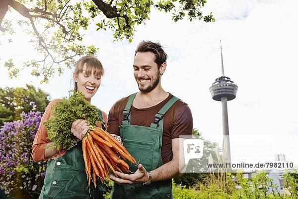 Deutschland  Köln  Junges Paar mit Karottenbüschel  lächelnd