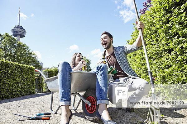 Deutschland  Köln  Junges Paar mit Bierflaschen  lächelnd