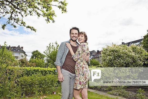 Deutschland  Köln  Junges Paar  das sich im Garten umarmt  lächelnd