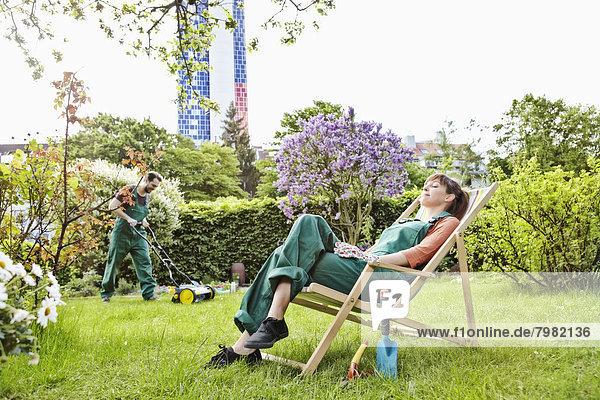 Junge Frau entspannt sich auf dem Liegestuhl beim Rasenmähen des Mannes