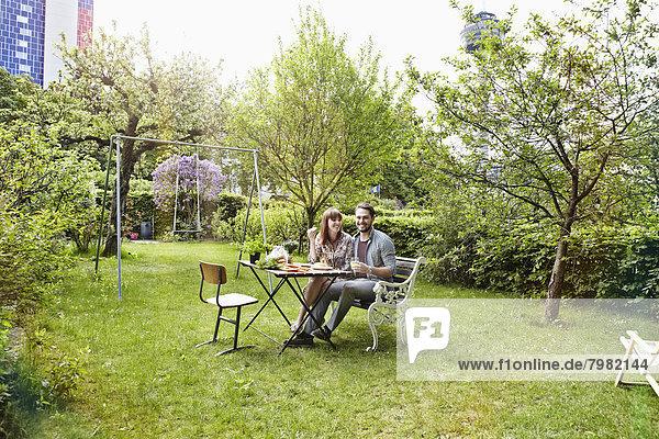 Deutschland  Köln  Junges Paar beim Frühstück im Garten