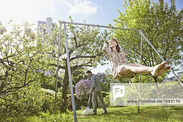 Junge Frau schwingt  während der Mann den Rasen im Hintergrund reibt.