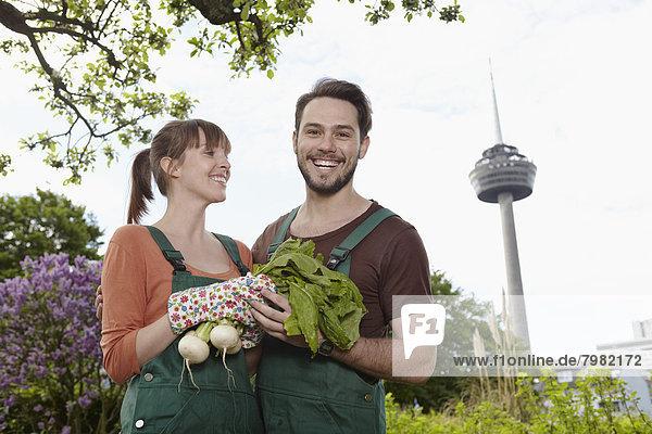 Deutschland  Köln  Junges Paar hält Zuckerrüben  lächelnd