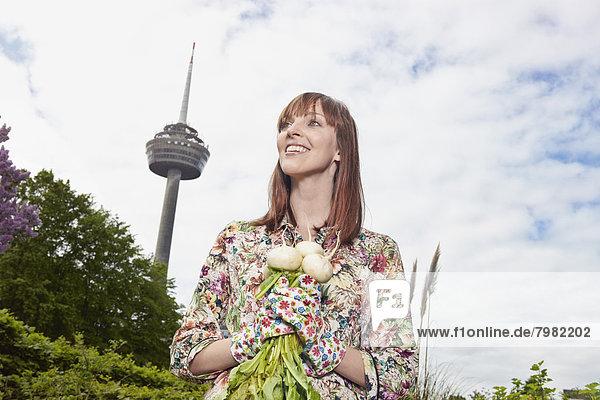 Junge Frau hält Zuckerrüben  lächelnd