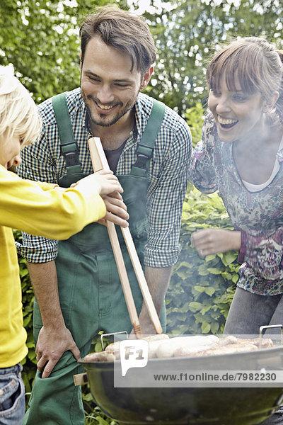Deutschland  Köln  Familie beim Grillen  lächeln