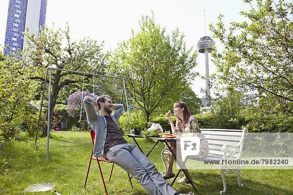 Deutschland  Köln  Junges Paar beim Frühstück im Garten  lächelnd