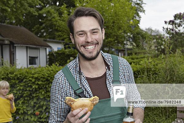 Porträt eines jungen Mannes mit Würstchen und Bierflasche im Hintergrund