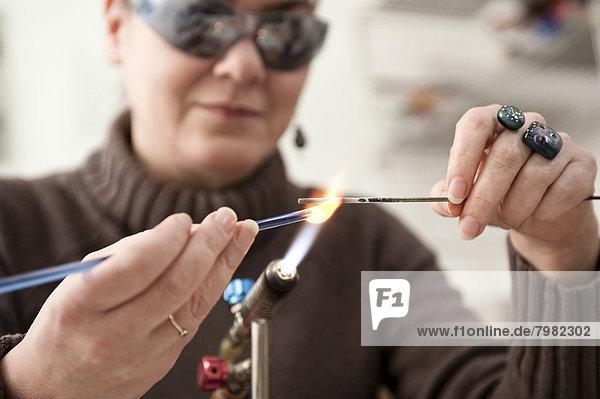 Mature woman making glass beads