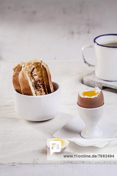 Ei im Eierbecher mit geröstetem Weißbrot und Kaffeetasse  Nahaufnahme Ei im Eierbecher mit geröstetem Weißbrot und Kaffeetasse, Nahaufnahme